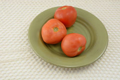 Three tomatoes on plate Royalty Free Stock Image