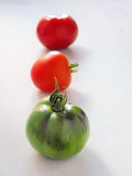 Three Tomatoes. Ripening Tomatoes. Red, Orange and Green Tomatoes Arranged on Light Gray Wooden Table Royalty Free Stock Images