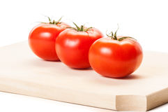 Three tomatoes standing in line on wooden board Stock Photos