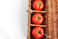 Three tomatoes in wicker box. With copy space stock photo