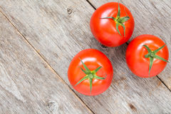 Three tomatoes on wooden background Stock Photography