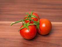 Three tomatos on wooden table. Three tomatos including some greens on a wooden table Stock Images