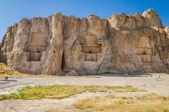 Ancient necropolis Naqsh-e Rustam in Fars province, Iran. Three tombs with reliefs in big rocks in desert, near to Shiraz and Persepolis stock photography
