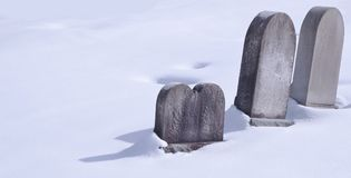 Three tombstones in snow on a sunny day stock images