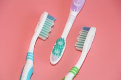 Three toothbrushes on a pink background. Oral hygiene stock photo