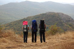 Three tourists with backpacks stand on a mountain slope. Stock Photography