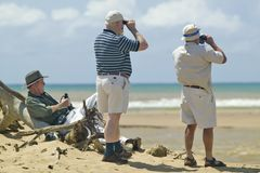 Three tourists with binoculars studing birdlife at Greater St. Lucia Wetland Park World Heritage Site, St. Lucia, South Africa Royalty Free Stock Photography