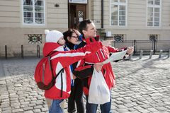 Three tourists are looking at the map of the city`s attractions Stock Photos