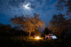 Three tourists sitting at a campfire near tent under trees and night sky with the moon Stock Photography