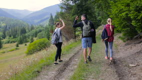 Three tourists stroll along the mountain road near the forest.  stock video