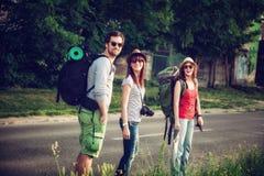 Three Tourists Walking On The Road Stock Photo