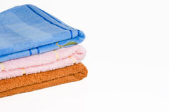 Three towels. Three built varicoloured towels on a white background Stock Photos
