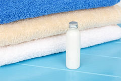 Three towels with little bottle of shampoo on a blue wooden back Royalty Free Stock Photo