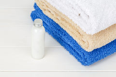 Three towels with one little bottle of shampoo on a white wooden Royalty Free Stock Image