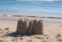 Three towers of sandy castle on the beach. Castle of sand with three towers by the sea royalty free stock image
