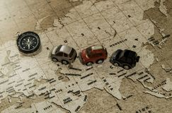 Three toy cars drive along the world map with compass Royalty Free Stock Images