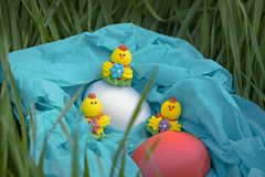 Three toy chickens and three easter eggs on the grass in a blue basket Royalty Free Stock Photos