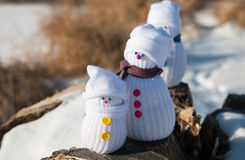 Three toy snowmen in a forest. Three toy snowmen stand on a log Stock Photo