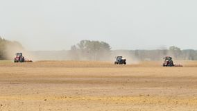 Three tractor manufacturing a dusty arid soil of brown color on the background of pine forest. Three tractors processing the dusty arid soil of brown color stock video