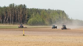 Three tractor manufacturing a dusty arid soil of brown color on the background of pine forest. Three tractors processing the dusty arid soil of brown color stock video footage