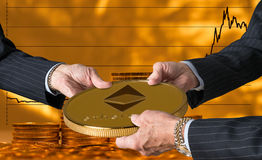 Three traders hands holding large ether or ethereum coin. Hands of three financial traders gripping ether or ethereum against a background of rising prices for Stock Photo