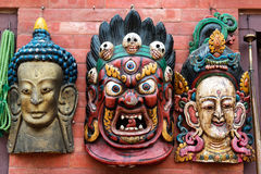 Three traditional Hindu masks hanging on wall at Kathmandu souve Stock Photos