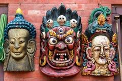 Three traditional Hindu masks hanging on wall at Kathmandu souve Stock Photos