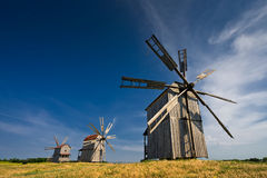 Three traditional windmills on the countryside at sunset stock image