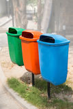 Three trash bin in different colors on a park Stock Photos