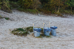 Three trash bins in the sand near the forest Royalty Free Stock Photos