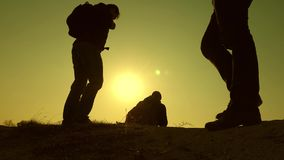 Three travelers descend from a hill in rays of sun one after other go beyond horizon. teamwork of business people. Three travelers descend from hill in rays of stock video