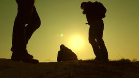 Three travelers descend from a hill in rays of sun one after other go beyond horizon. teamwork of business people stock video