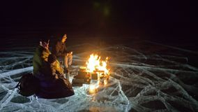Three travelers by fire right on ice at night. Campground on ice. Tent stands next to fire. Lake Baikal. Nearby there is. Car. People are warming around stock video footage