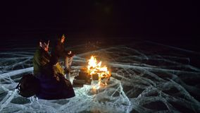 Three travelers by fire right on ice at night. Campground on ice. Tent stands next to fire. Lake Baikal. Nearby there is. Car. People are warming around stock video