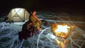 Three travelers by fire right on ice at night. Campground on ice. Tent stands next to fire. Lake Baikal. Nearby there is. Car. People are warming around stock footage