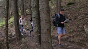Three travelers two girls and a guy are studying the map. Walking tour of tourists through the forest with backpacks.  stock video