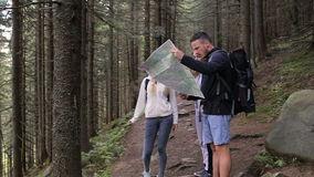 Three travelers two girls and a guy are studying the map. Walking tour of tourists through the forest with backpacks.  stock footage