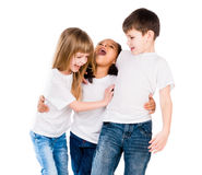 Three trendy children with different complexion laugh and embrace each other. Three trendy children with different complexion laugh embracing each other isolated Stock Image