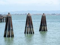 Triangular wooden markers sticking out of the water at a dock on. Three triangular wooden markers sticking out of the water at a dock on a sunny day Stock Photo