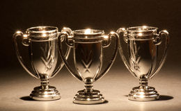 Three Trophies. Three shiny trophies standing in a row stock photography