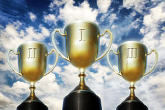 Three trophy cups against cloudy sky Stock Photos