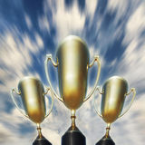 Three trophy cups against windy sky Stock Photography