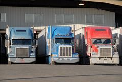 Three trucks at warehouse. Three semi trucks at warehouse waiting to be loaded Royalty Free Stock Photos