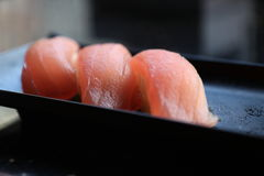 Three tuna nigiri sushi. On a black plate Stock Photography