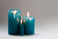 Three turquoise candles with a burning wick. Different size candles, motion flame. Family day concept. Gradient Stock Photo