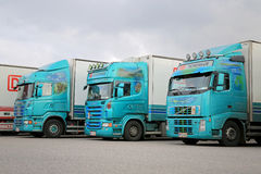 Three Turquoise Trailer Trucks. NAANTALI, FINLAND - OCTOBER 11, 2014: Fleet of three colorful trailer trucks on a yard. According to Statistic Finland, a total stock photo