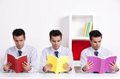 Three twin businessman reading books Royalty Free Stock Images
