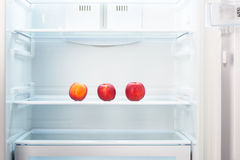 Three two-colored orange and red peaches on shelf of open empty refrigerator Stock Photos