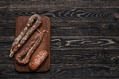 Three types of dried sausage on cutting board.Top view Royalty Free Stock Photo