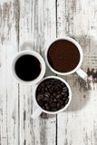 Three types of coffee - ground, grain and beverage in cups. On white background, top view Royalty Free Stock Photos